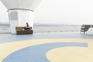 Woman sitting on deck of cruise liner looking at her smartphone - ONBF000043