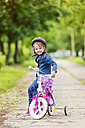 Smiling girl on bike with training wheels - HAPF000488