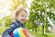 Happy girl holding ball in park - HAPF000494
