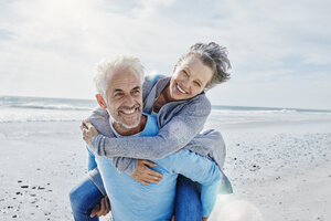 Man giving his wife a piggyback ride on the beach - RORF000203
