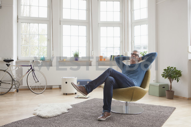 Relaxed mature man at home sitting in chair - RBF004535 - Rainer Berg/Westend61