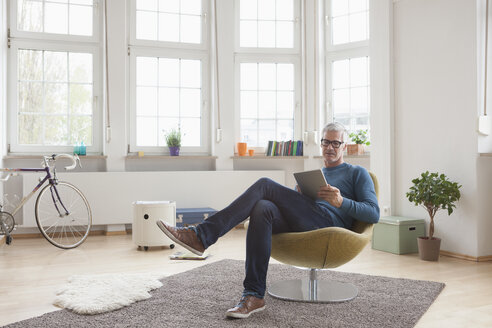 Mature man at home sitting in chair using digital tablet - RBF004538