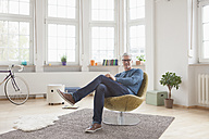 Relaxed mature man at home sitting in chair - RBF004541