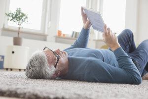 Mature man at home lying on floor using digital tablet - RBF004544
