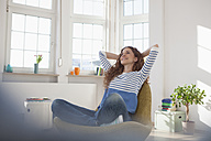 Relaxed woman at home sitting in chair - RBF004553