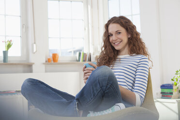 Smiling woman at home sitting in chair - RBF004559