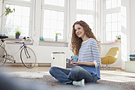 Smiling woman at home sitting on floor - RBF004562