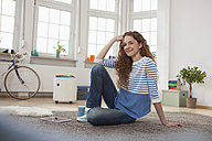 Smiling woman at home sitting on floor - RBF004565