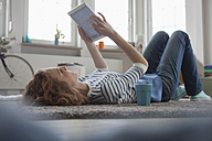 Woman at home lying on floor using digital tablet - RBF004571