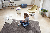 Woman at home sitting on floor using digital tablet - RBF004574