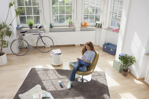 Woman at home sitting in chair using digital tablet - RBF004580