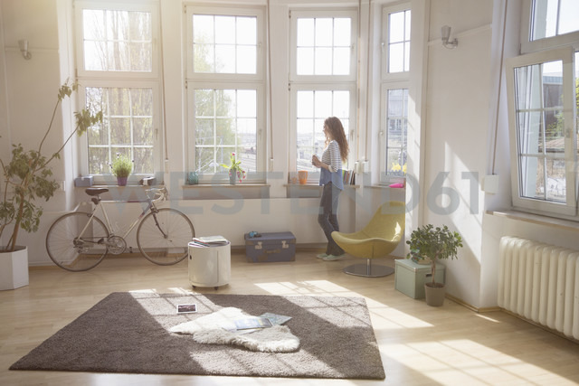 Woman at home looking out of window - RBF004583