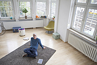 Relaxed mature man at home sitting on floor - RBF004589