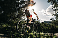 Mountain biker on the move in backlight - JRFF000715