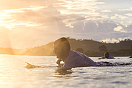Indonesia, Sumbawa island, Surfer lying on surfboard in the evening - KNTF000287