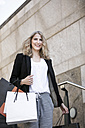 Portrait of smiling woman with several shopping bags - GDF000999
