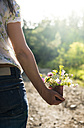 Woman holding small bucket with wildflowers in her hand - DEGF000819