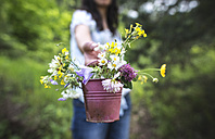 Woman offering small bucket with wildflowers - DEGF000822