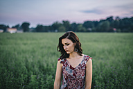 Portrait of a melancholic woman wearing a dress in a green field - LCU000011