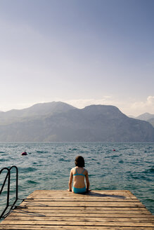 Italy, Brenzone, back view of girl sitting on jetty - LVF004904