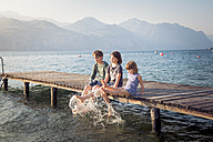 Italy, Brenzone, three children sitting side by side on jetty splashing with water - LVF004910