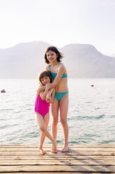 Italy, Brenzone, two little sister standing on jetty - LVF004913
