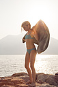 Italy, Brenzone, girl in bikini drying herself with towel at lakeshore - LVF004916
