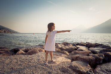 Italy, Brenzone, little girl standing at lakeshore pointing on something - LVF004919
