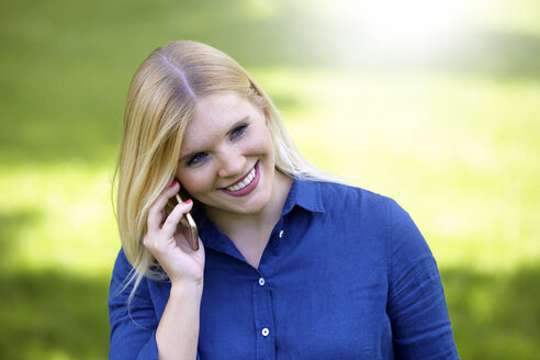 Smiling young woman telephoning with smartphone in a park - FMKF002714