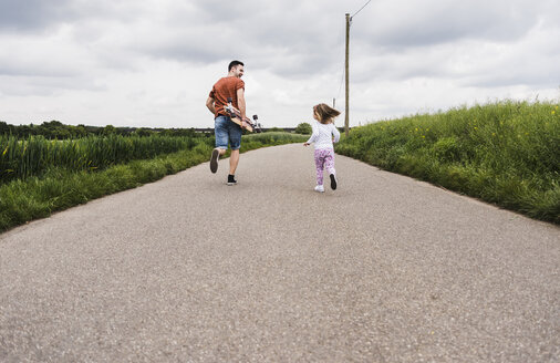 Father with skateboard and daughter running on country lane - UUF007406