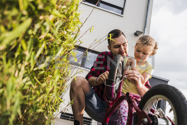 Father and daughter repairing bicycle together - UUF007415