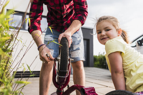 Father and daughter repairing bicycle together - UUF007418