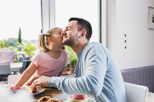 Daughter kissing father at breakfast table - UUF007424