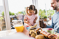 Father and daughter having breakfast together - UUF007427