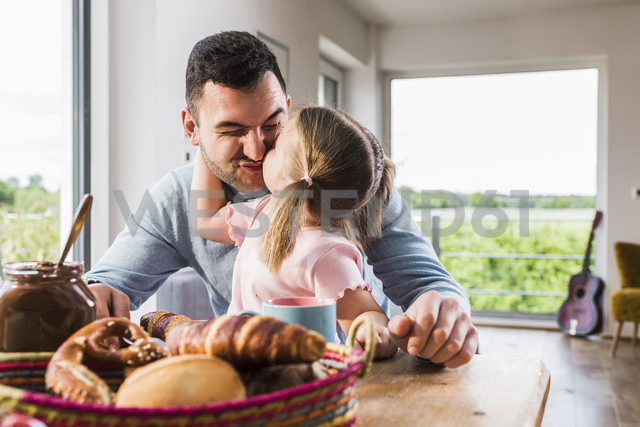 Daughter kissing father at breakfast table - UUF007433