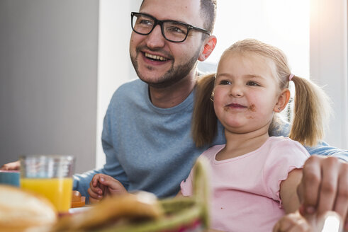 Happy father and daughter having breakfast together - UUF007436