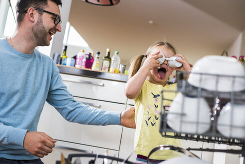 Playful daughter and father clearing dishwasher - UUF007451