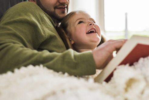Happy daughter looking at father reading a book at home - UUF007454