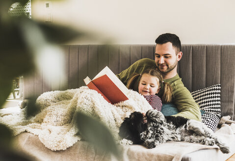 Father and daughter with dog reading a book at home - UUF007457