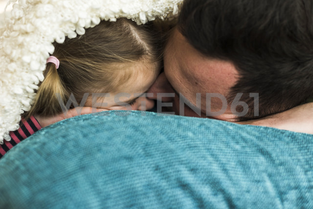 Father and daughter cuddling at home - UUF007460
