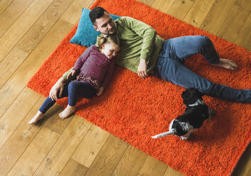 Father and daughter lying on carpet on the floor with dog - UUF007463