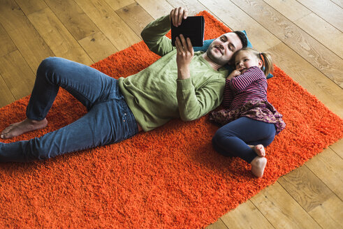 Father and daughter lying on carpet on the floor using digital tablet - UUF007466
