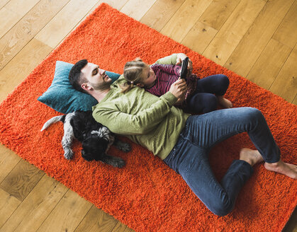 Father and daughter lying on carpet on the floor using digital tablet - UUF007472