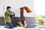 Father and daughter having a pillow fight - UUF007475