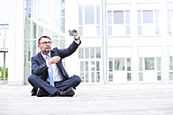 Businessman sitting outdoors taking a selfie - MAEF011778