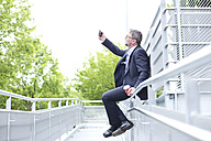 Businessman sitting on railing outdoors taking a selfie - MAEF011784