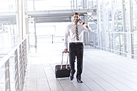 Businessman with luggage and cell phone on the move - MADF000884