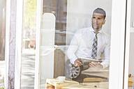 Businessman holding digital tablet in a cafe - MADF000917