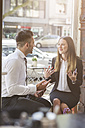 Businessman and businesswoman discussing in a cafe - MADF000923