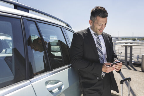Businessman leaning against car looking at cell phone - MADF000932